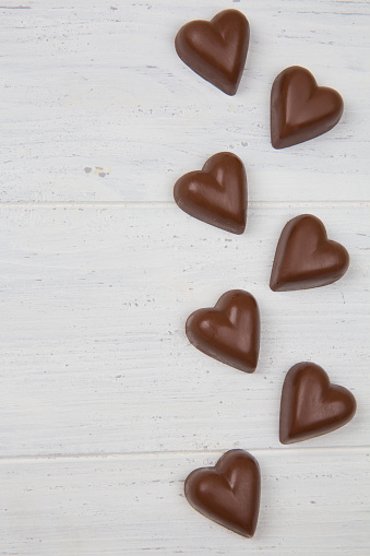 Milk chocolate on a white wooden background. Heart shaped candy. Valentine's Day