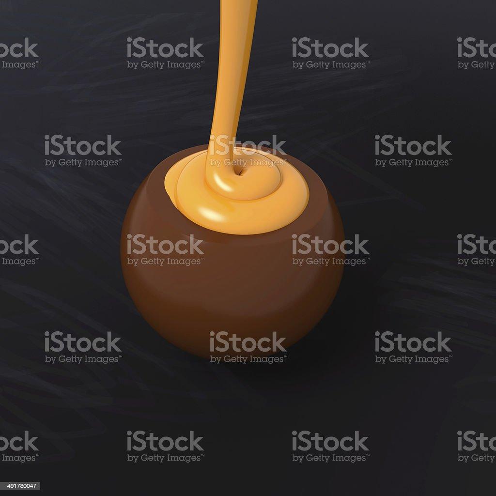 Milk chocolate praline with orange cream filling on blackboard stock photo