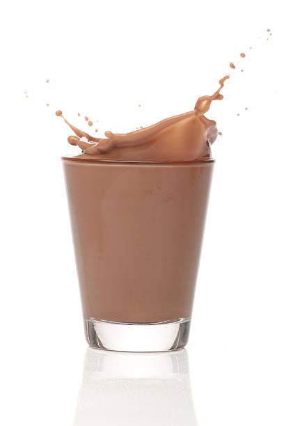 Milk chocolate splash over white background stock photo