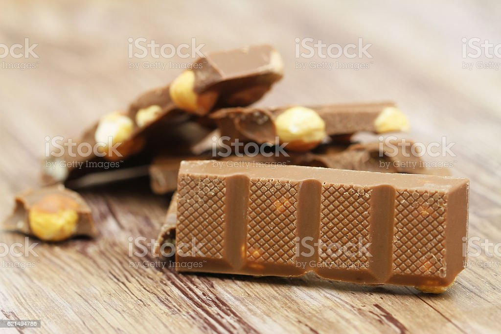 Milk chocolate with whole hazelnuts on wooden surface foto stock royalty-free