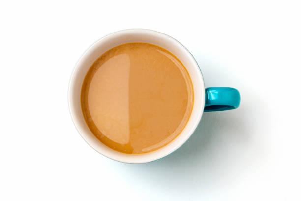 Café de lait dans la tasse en céramique bleue sur le fond blanc - Photo