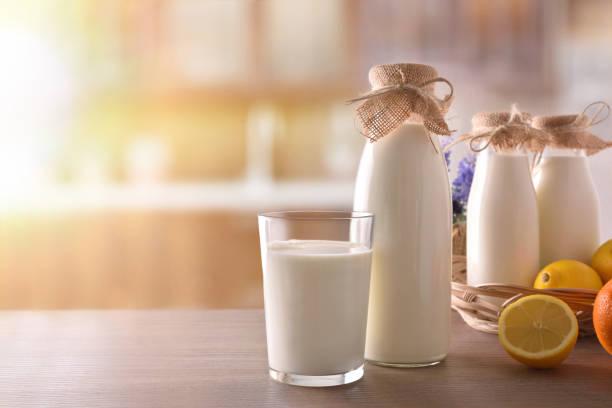 melk containers op houten tafel in zonnige rustieke keuken - calcium stockfoto's en -beelden