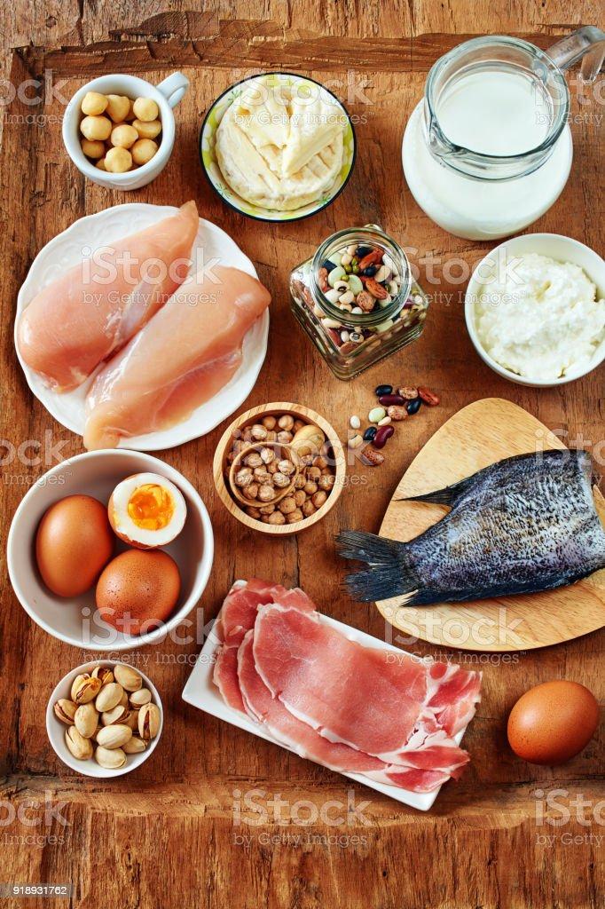 Milch, Quark, Eiern, Fisch und Huhn Fleisch, Bohnen, Kichererbsen und Nüssen auf Holztisch. – Foto