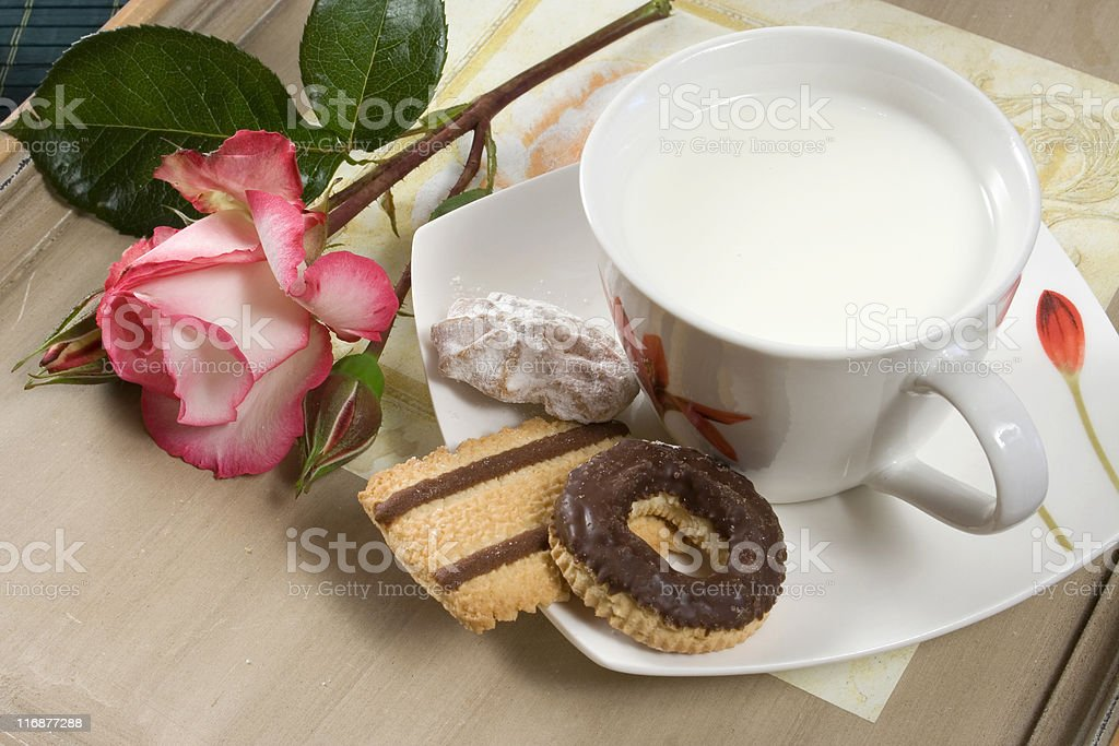 Milk cup with rose flower and chocolate biscuits royalty-free stock photo