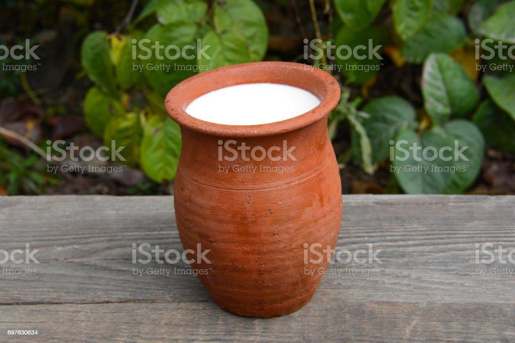 Milk in a clay pot stock photo