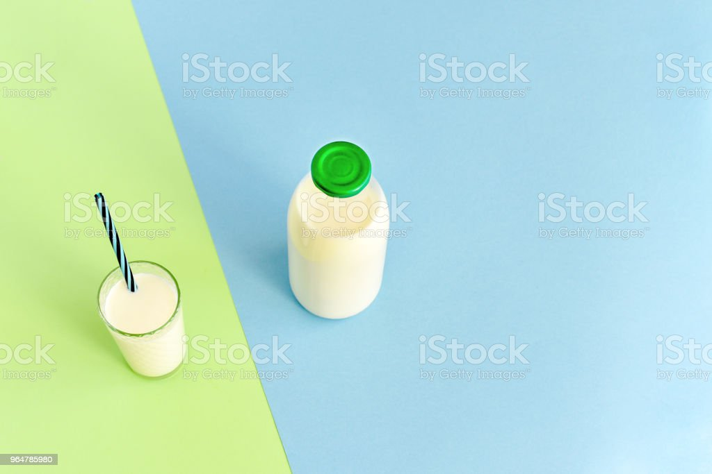 Milk in a glass bottle and a transparent glass with straw royalty-free stock photo
