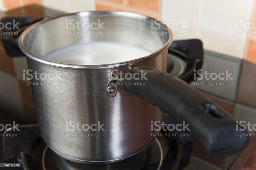 Milk in a saucepan on a gas stove burner stock photo