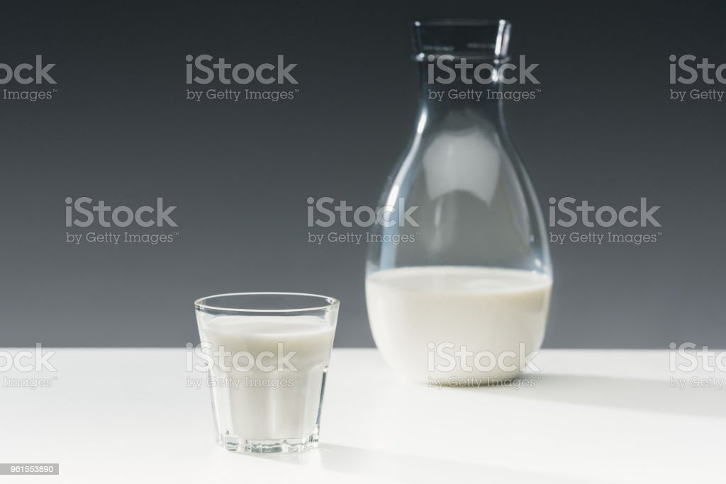 Milk in glass and bottle on table on grey background