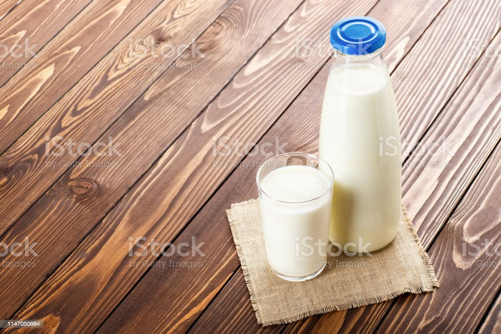 milk in glass and bottle with napkin on wooden table