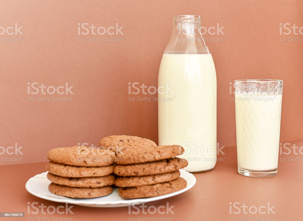 Milk in glass bottle and transparent glass and cookies on white plate royalty-free stock photo