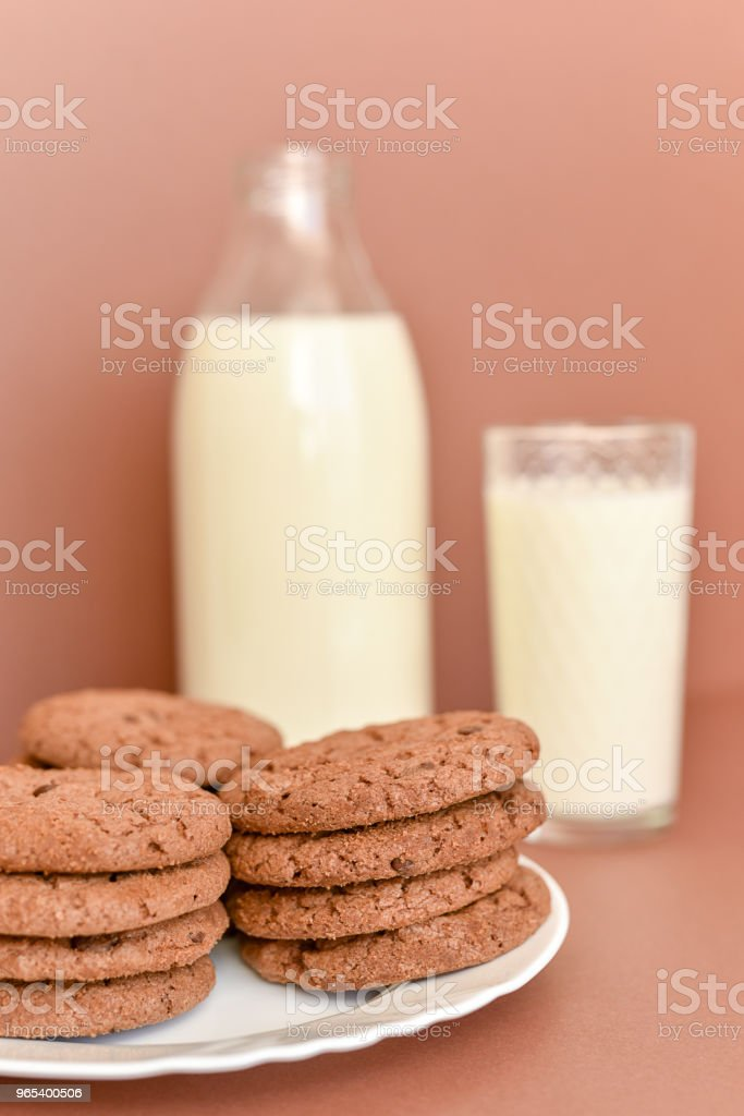 Milk in glass bottle and transparent glass and cookies on white plate zbiór zdjęć royalty-free