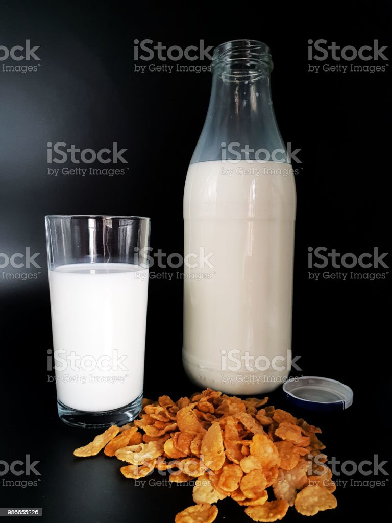 Milk in glass with bottle on black background