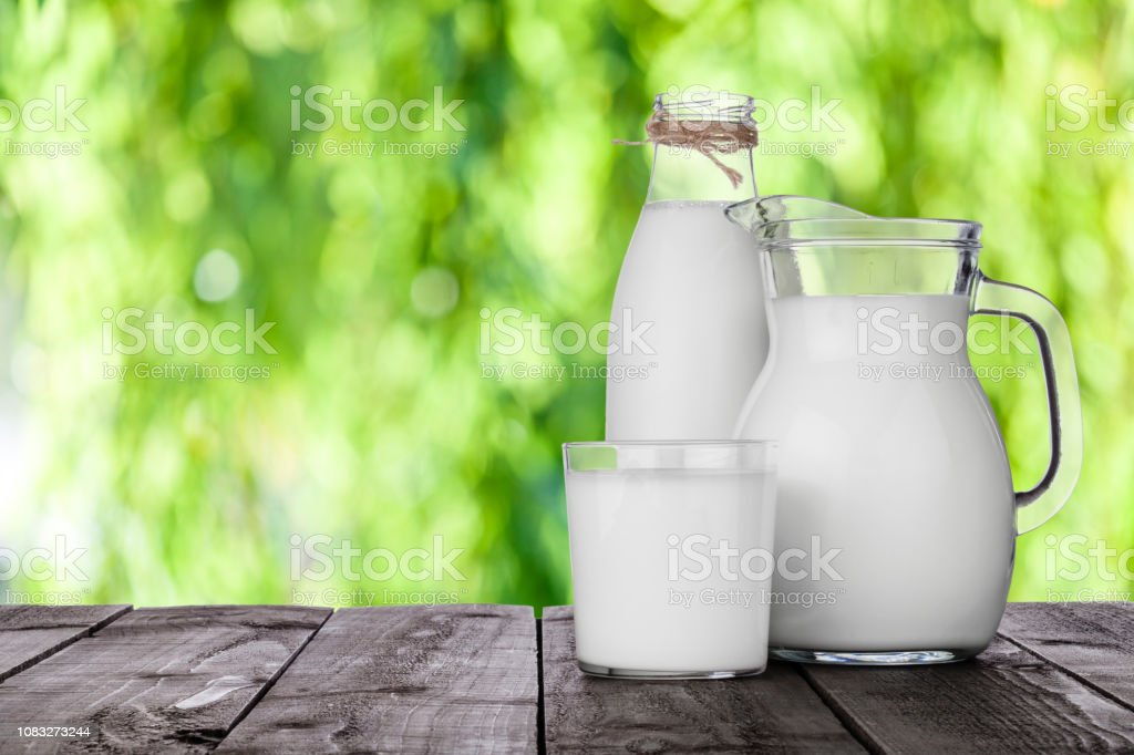Milk jar, milk bottle and milk glass shot on rustic wooden table...