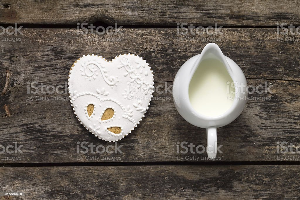 Milk Jug with big Gingerbread Cookies on old wood background stock photo