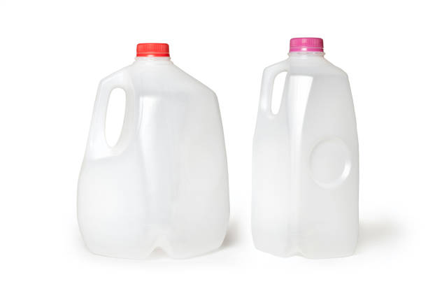 Milk Jugs on a White Background Horizontal photograph of 2 milk jugs, half gallon and gallon jug, lined up in a row. The labels are off and the jugs are empty and placed on a white background. gallon stock pictures, royalty-free photos & images