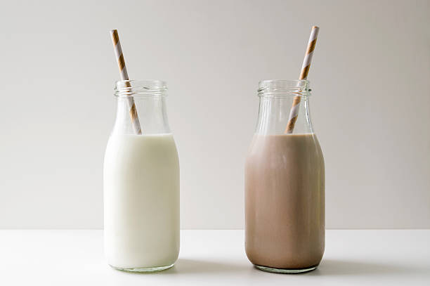 milk jugs regular and chocolate side by side on white Regular white milk sitting next to chocolate milk.  The milk is in old fashioned glass milk jugs with striped straws in each container.  Studio shot on a white surface with a gray background. chocolate milk stock pictures, royalty-free photos & images