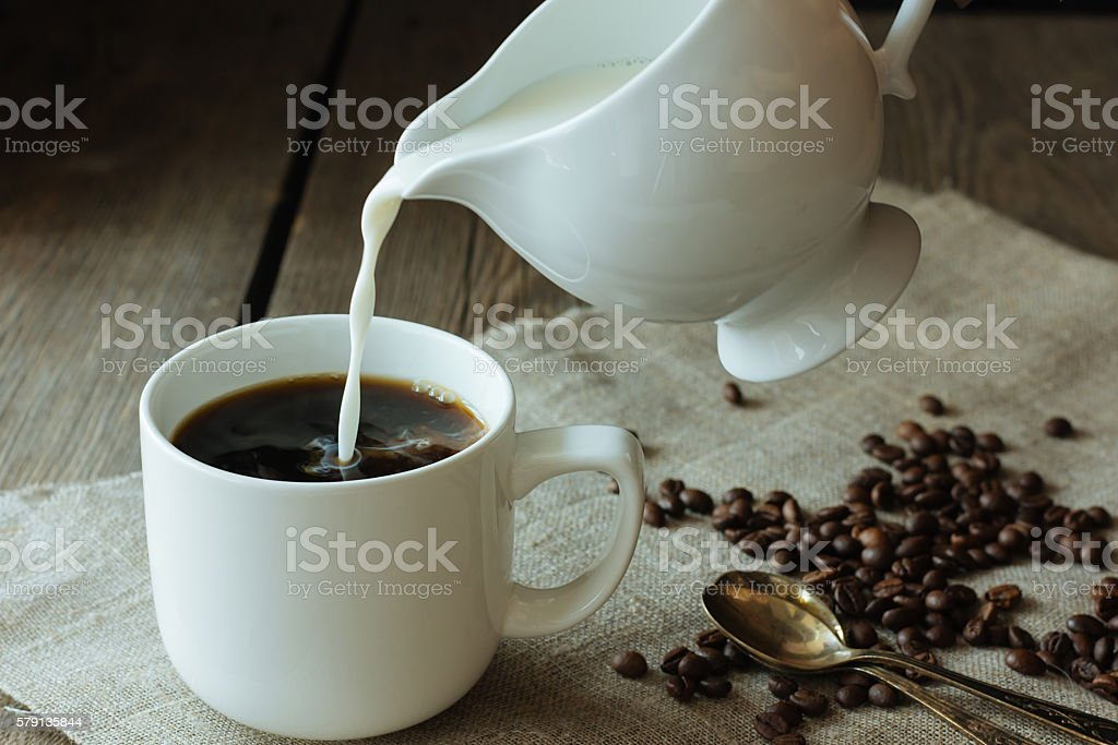 Milk pouring in the cup of black coffee stock photo