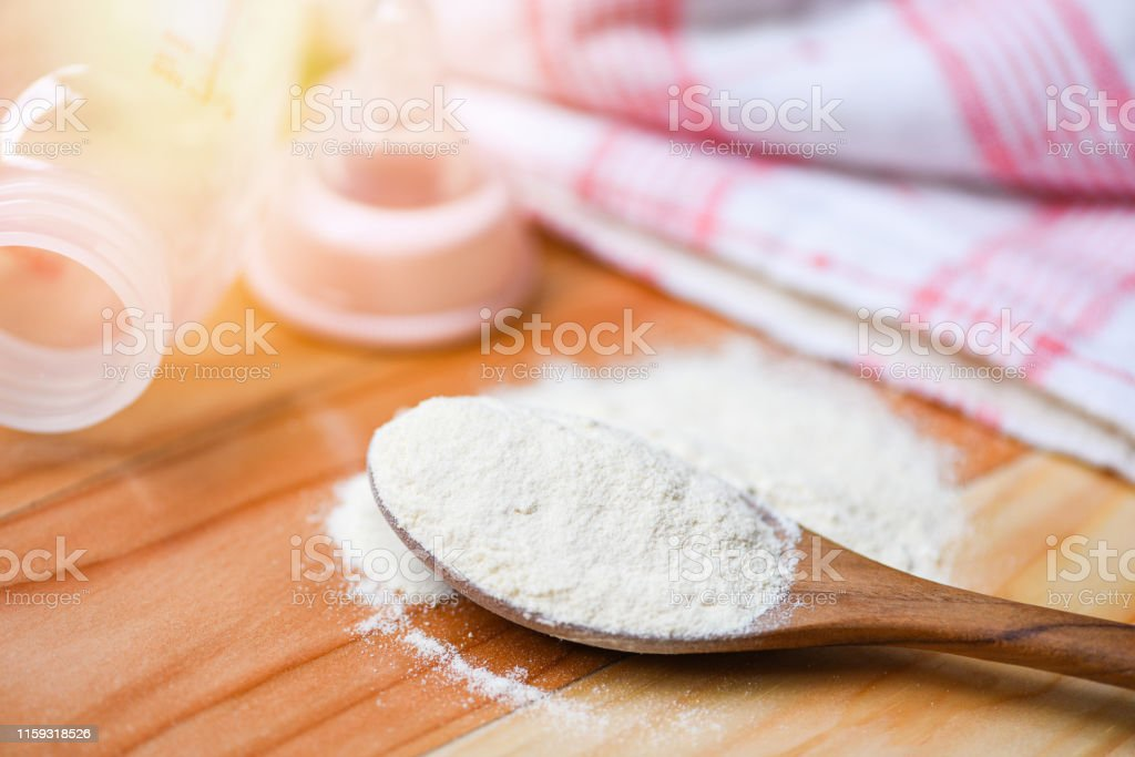 Milk powder spoon with milk bottle baby on wooden table