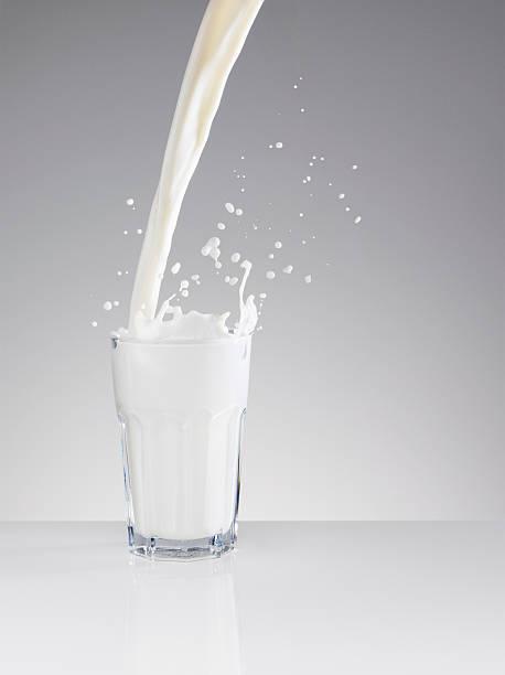 Milk splashing in full glass stock photo