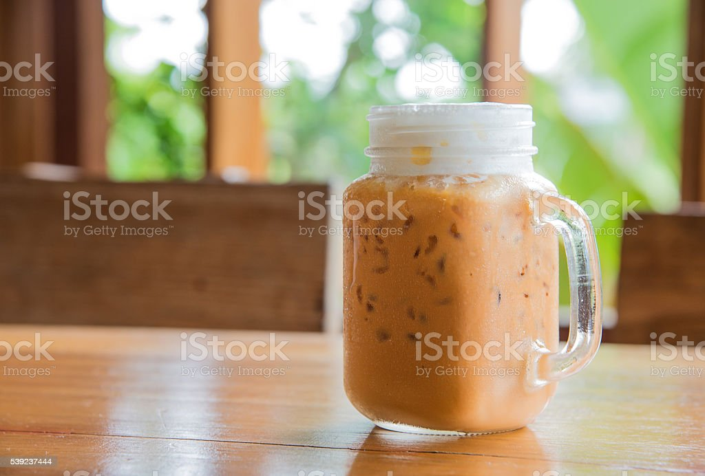 Milk tea with ice in Glass handle on wooden table. royalty-free stock photo