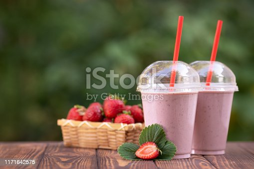 two disposable glasses of strawberry milkshake or smoothie and fresh ripe berries in basket on wooden table outdoors