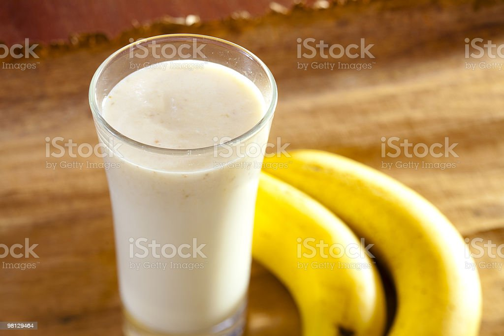 A milkshake on a wooden table adjacent to two bananas  royalty-free stock photo