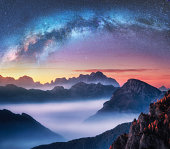 Milky Way above mountains in fog at night in summer. Landscape with alpine mountain valley, low clouds, colorful starry sky with milky way at sunset. Aerial view. Passo Giau, Dolomites, Italy. Space