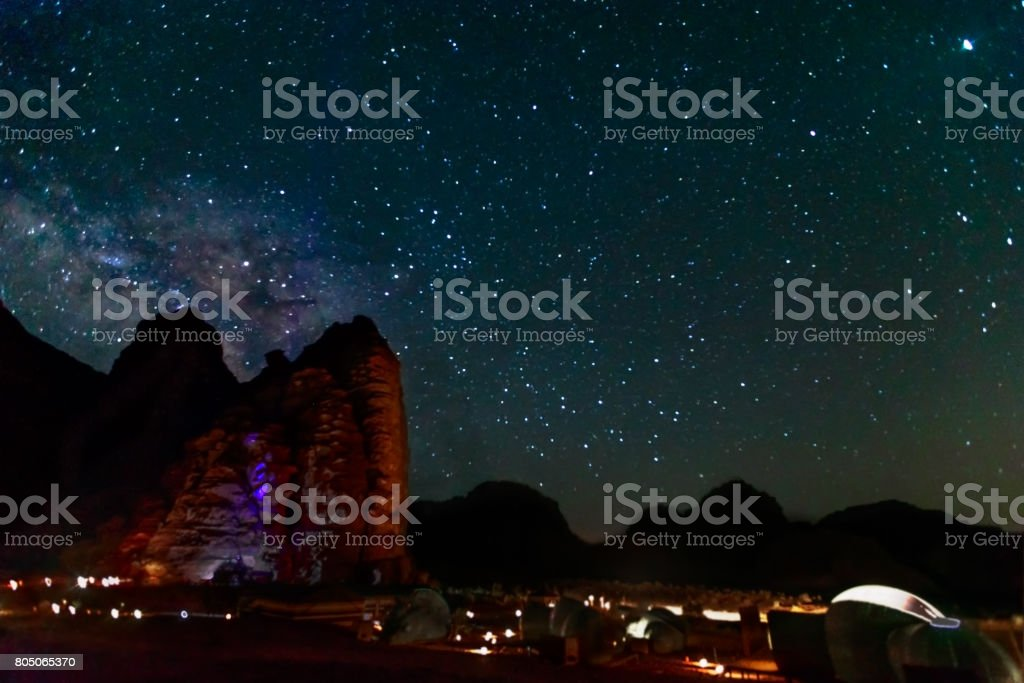 Milky Way and a lot of stars over the mountain at Wadi Rum desert.  Sky at night and silhouette of mountain with wonderful landscape in summer, concept for space background and traveling. stock photo