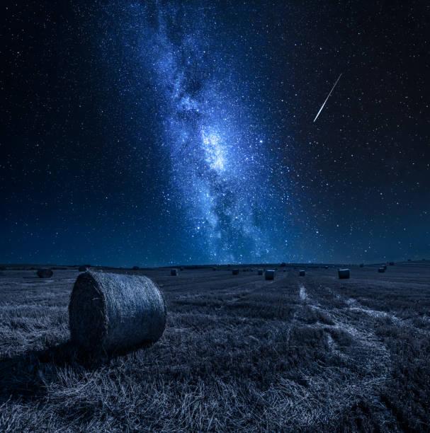 Milchstraße und Feld mit Heu in der Nacht – Foto