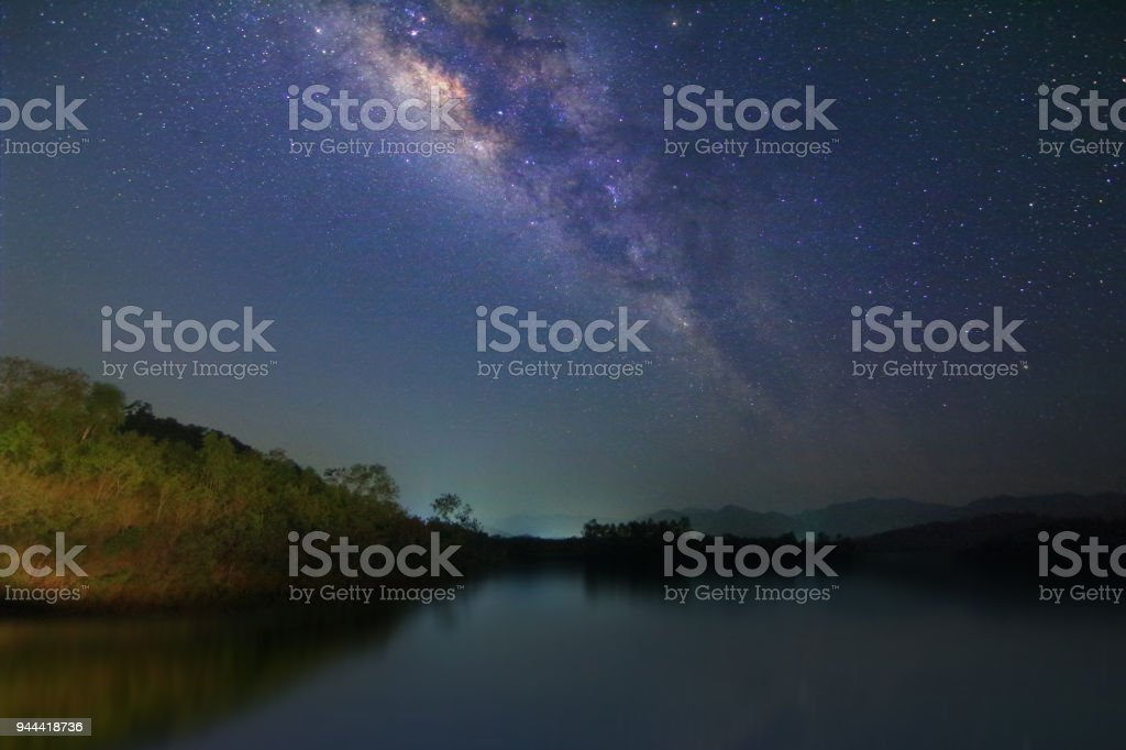 Milky way and many stars on night sky at at lake and mountain in Thailand. stock photo