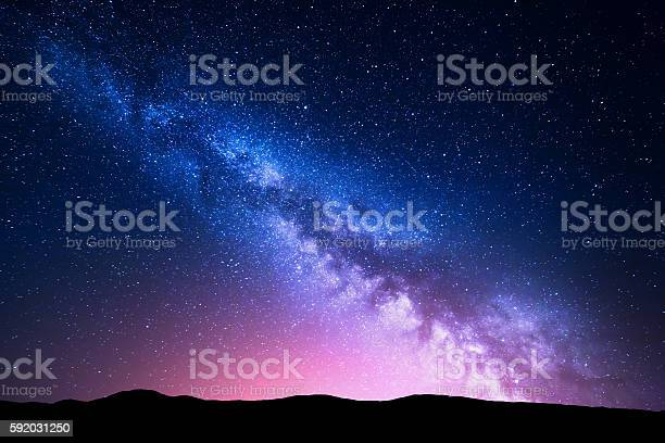 Photo of Milky Way and pink light at mountains. Night colorful landscape.