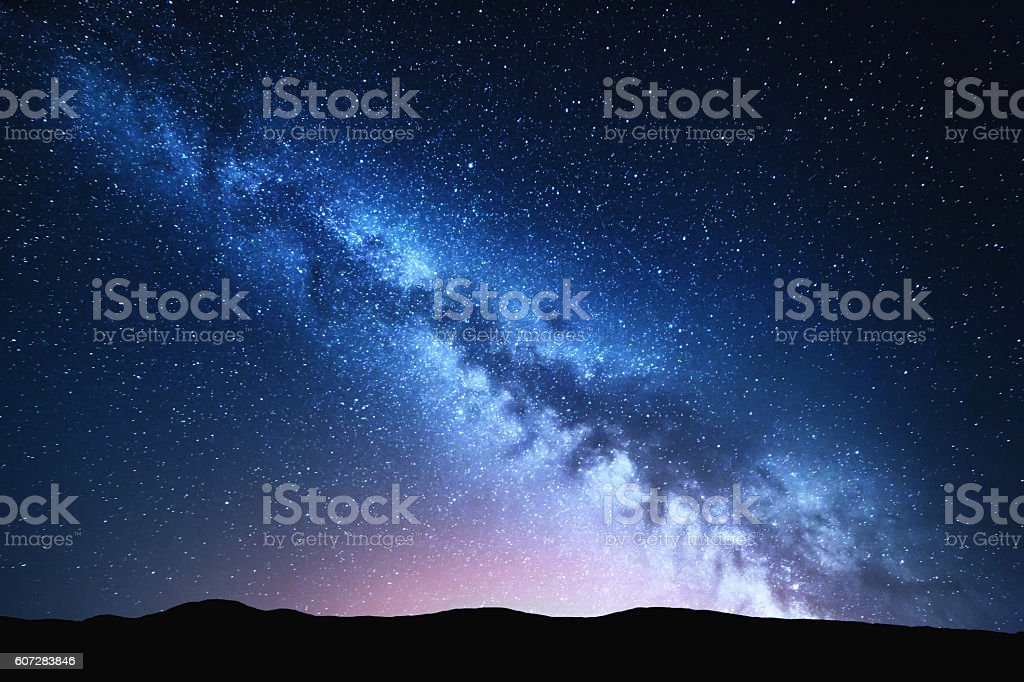 Milky Way and pink light at mountains. Night colorful landscape. stock photo