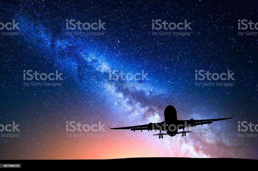 Vía Láctea y la silueta de un avión. Paisaje con avión de pasajeros vuela en el cielo estrellado por la noche. Fondo del espacio. Avión comercial en el fondo de color vía Láctea. Avión - foto de stock