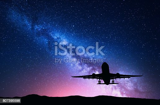 istock Milky Way and silhouette of a airplane. Landscape with passenger airplane is flying in the starry sky at night. Space background. Landing airliner on the background of colorful Milky Way. Aircraft 807395598