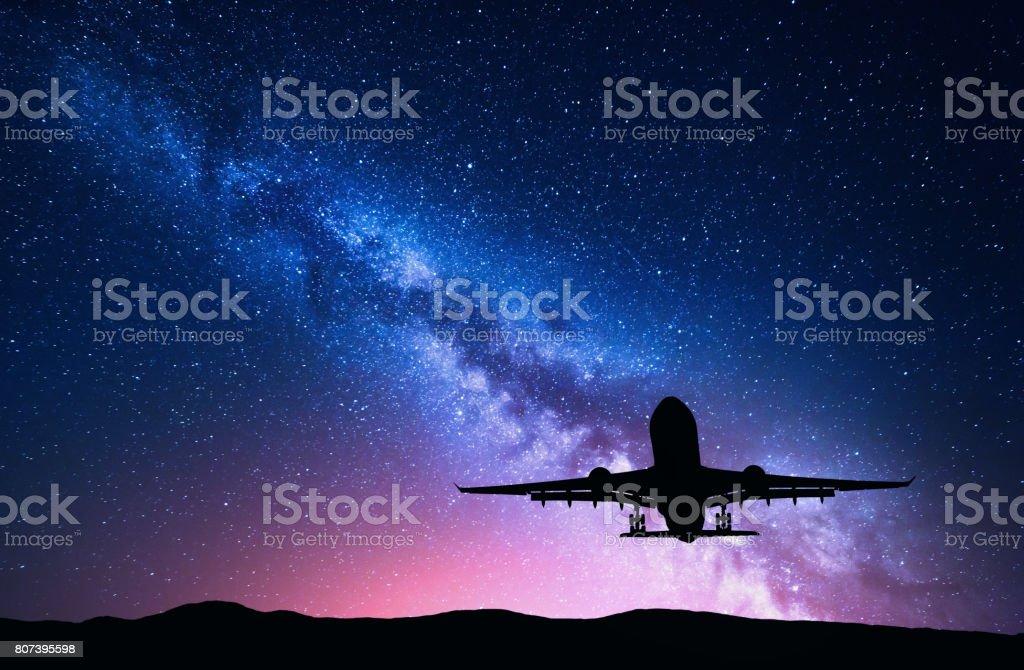 Vía Láctea y la silueta de un avión. Paisaje con avión de pasajeros vuela en el cielo estrellado por la noche. Fondo del espacio. Aterrizaje de avión en el fondo de color vía Láctea. Avión - foto de stock