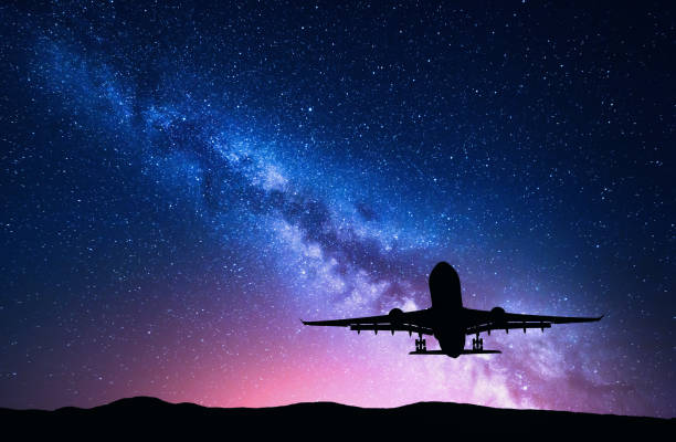 milky way and silhouette of a airplane. landscape with passenger airplane is flying in the starry sky at night. space background. landing airliner on the background of colorful milky way. aircraft - den belitsky foto e immagini stock