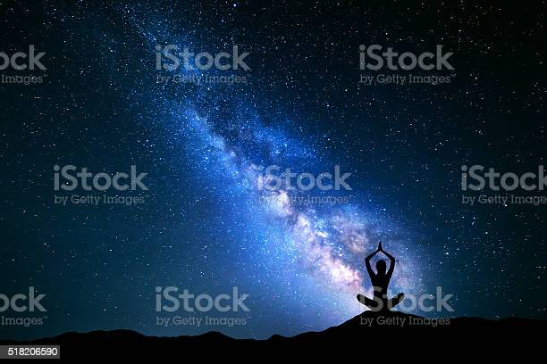 Photo of Milky Way and silhouette of a girl practicing yoga