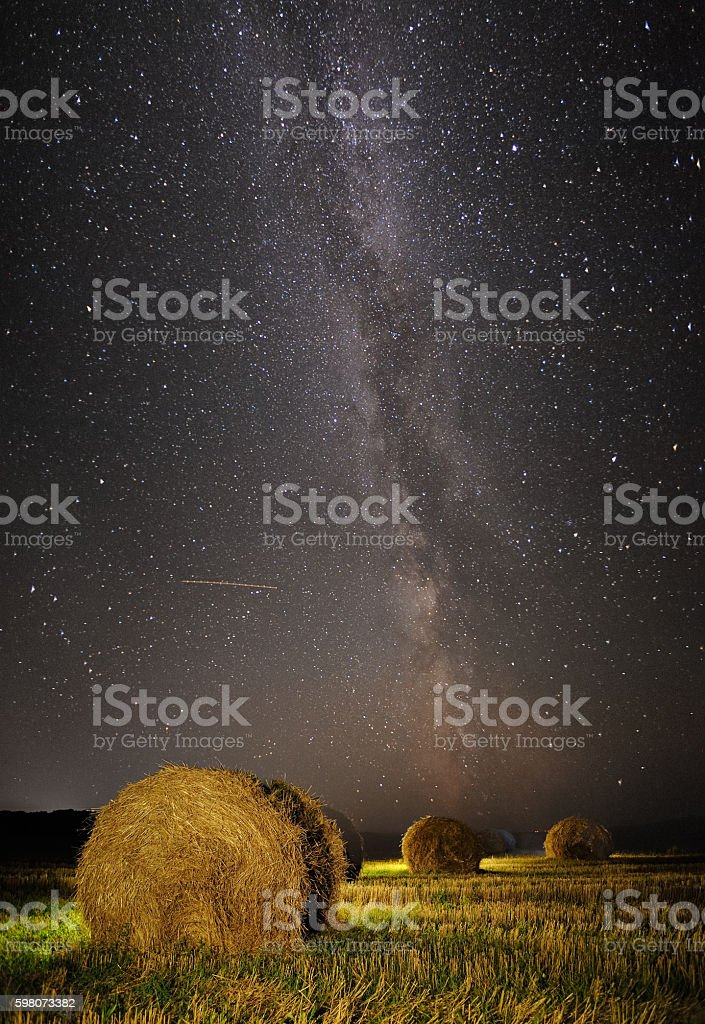 Milky Way and wheat field with haystacks stock photo
