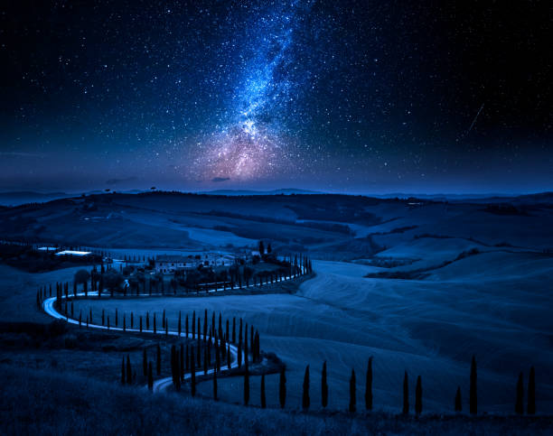 Milky way and winding road with cypresses, Tuscany Milky way and winding road with cypresses, Tuscany pienza stock pictures, royalty-free photos & images