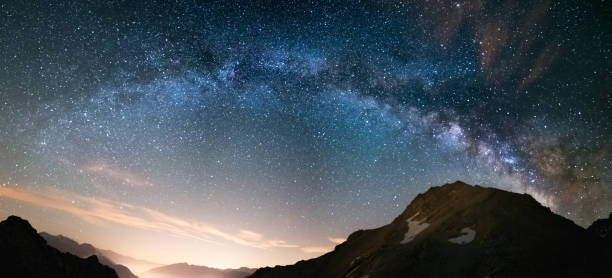 Milky Way arch and starry sky on the Alps. Panoramic view, astro photography, stargazing. Light pollution in the valley below. stock photo