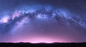 istock Milky Way arch. Fantastic night landscape with bright arched milky way, purple sky with stars, pink light and hills. Beautiful scene with universe. Space background with starry sky. Galaxy and nature 1269949331