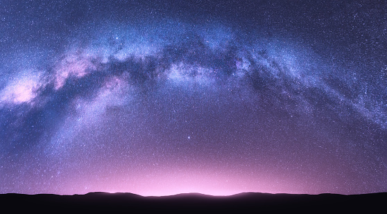 Milky Way arch. Fantastic night landscape with bright arched milky way, purple sky with stars, pink light and hills. Beautiful scene with universe. Space background with starry sky. Galaxy and nature