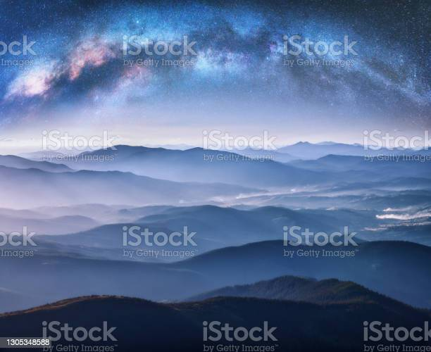 Photo of Milky Way arch over the mountains in fog at starry night in summer. Landscape with blue sky with stars, arched Milky Way, trees on the foggy hills, mountain peaks. Space and galaxy. Aerial view