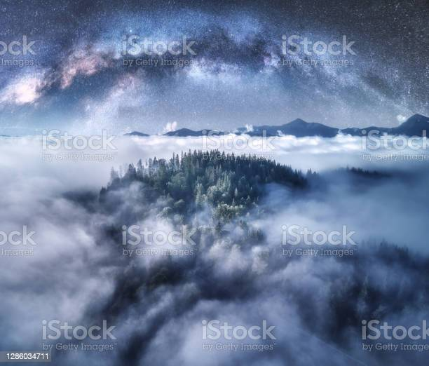 Photo of Milky Way arch over the mountains in low clouds at starry night in summer. Landscape with sky with stars, arched Milky Way, trees on the hill in fog, mountain peaks. Space and galaxy. Aerial view