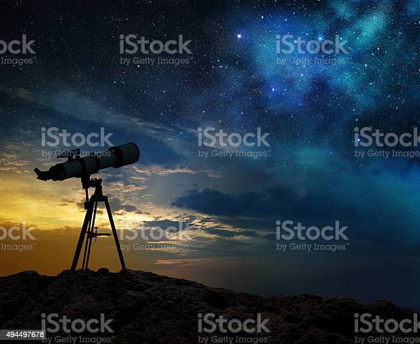 Photo of milky way at dawn and silhouette of a telescope