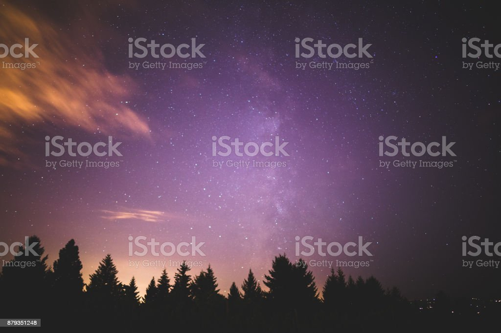 Milky Way, City Light, and Clouds Over Forest Trees stock photo