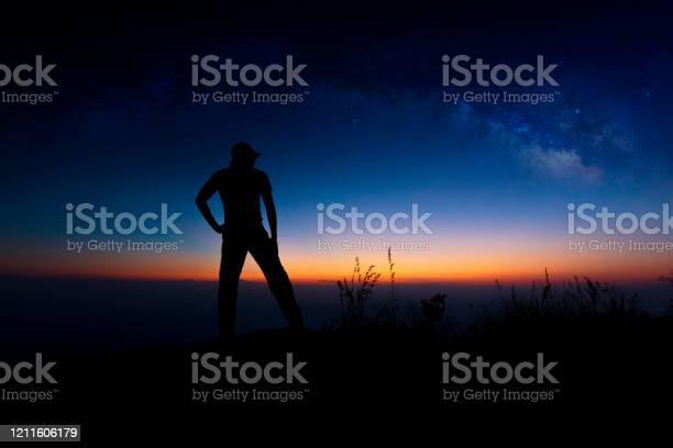 Photo of Milky Way. Colorful night sky with stars and silhouette of a standing man on the stone. Blue milky way with man on the mountain. High Rocks. Background with galaxy and silhouette of a man. Universe