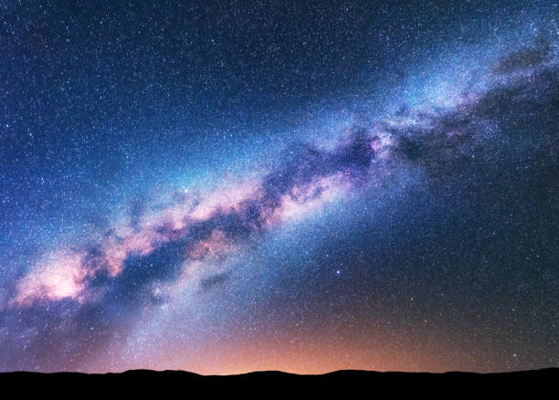 milky way. fantastic night landscape with purple milky way, sky full of stars, yellow light and hills. shiny stars. beautiful scene with universe. space background with starry sky. astrophotography. - den belitsky foto e immagini stock