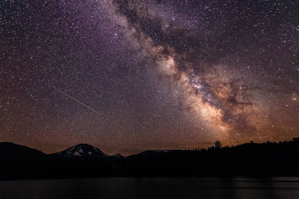 Milky way galaxy and a meteor streaking across a clear night sky stock photo