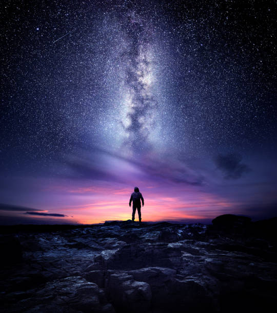 Milky Way Galaxy Night Landscape Night time long exposure landscape photography. A man standing in a high place looking up in wonder to the Milky Way galaxy, photo composite. outer space stock pictures, royalty-free photos & images